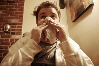 man sick blowing nose sickness
