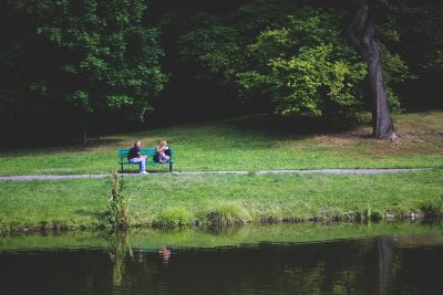 couple talking on bench green