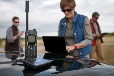 woman using satellite phone on car hood