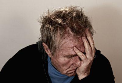 old man rubbing head headache