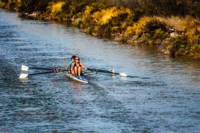women rowing boat river