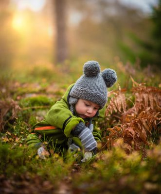 child playing in grass forest